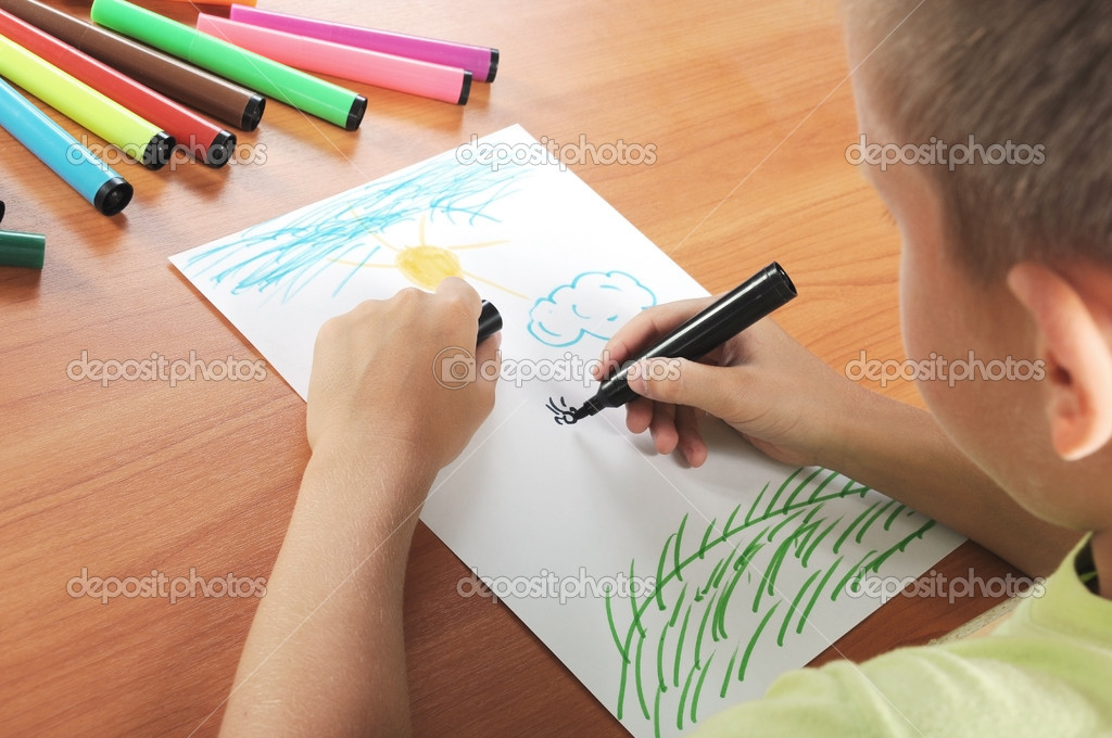 Child draws green grass and sun on white paper by colour pensil  Stock Photo #1108443