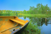 Boat with holey on lake under blue sky — Stock Photo