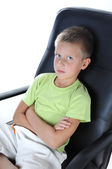 Boy sit on chair and look at camera — Stock Photo