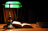 Green table lamp and opened book — Stock Photo
