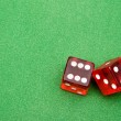 Red dice against green background — Stock Photo #2561594
