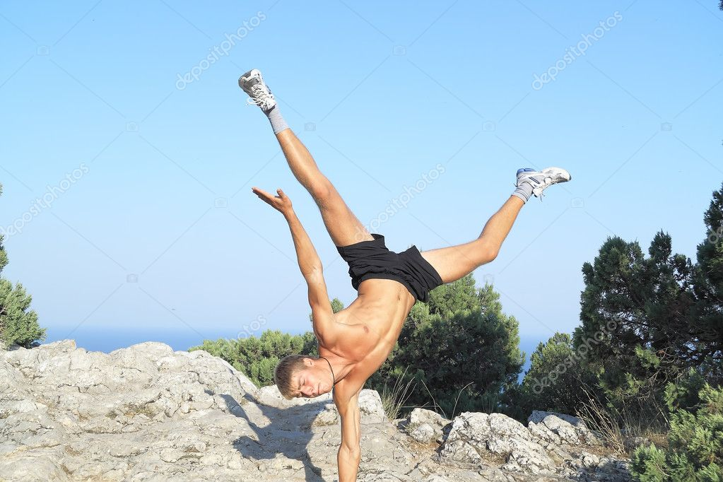 Young gymnast sdeal rack on one hand in the mountains of Crimea — Stock Photo #1215251