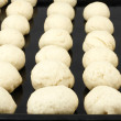 Harvesting of dough for buns - Stock Photo