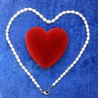 Red heart and pearly neacklace on blue v - Stock Photo