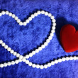 Red heart and pearly neacklace on blue v — Stock Photo
