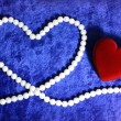 Red heart and pearly neacklace on blue v — Stock Photo #1113831
