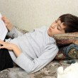 Boy on bed with cat, reading bok — Stock Photo