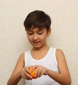 Boy, peeling the orange — Stock Photo