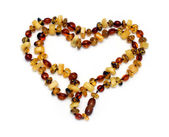 Heart shape from amber necklace — Stock Photo