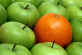 Different concepts - orange between appl — Stock Photo