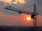 Lifting crane and sunset — Stock Photo