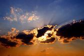 De stralen van de zon achter de donkere wolken in de hemel — Stockfoto