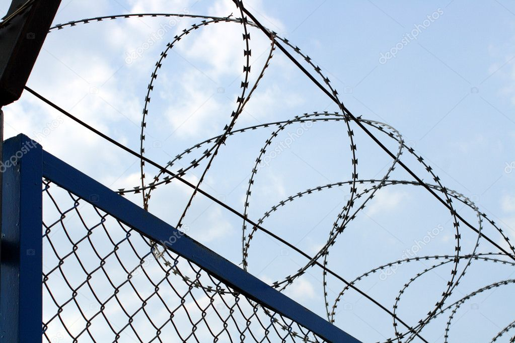 Fence with barbed wire close-up under blue sky — Stock Photo #1114407