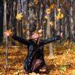 Royalty-Free Stock Photo: Beautiful girl throwing up autumn leaves