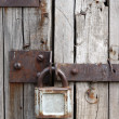 Old rusty padlock on wooden door - Stock Photo