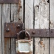 Stock Photo: Old rusty padlock on wooden door