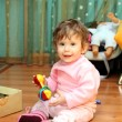 Baby girl with toy on floor — Stock Photo
