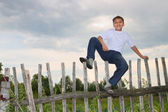 Happy boy sitting on fence — Stock Photo