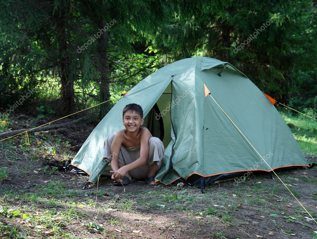 Happy boy near camping tent in summer forest  Stock Photo #2458026