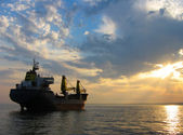 Dry cargo ship at sunset — Stockfoto
