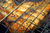Salmon steak cooking on a grill — Stock Photo