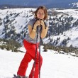Girl with skis staying on a mountain slo — Stock Photo