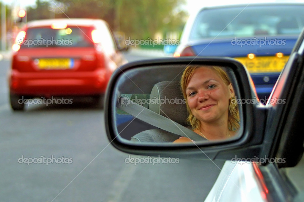 The face of a young woman driving a car in the rear view mirror — Stockfoto #1305580