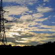 Sun setting behind electricity pylon — Stock Photo