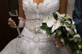 Bride hold bouquet and wine — Stock Photo