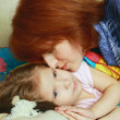 Mum kisses a daughter before a dream — Stock Photo