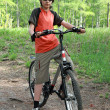 The teenager in a wood on a bicycle - Stockfoto
