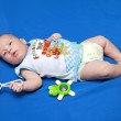 The baby of 3,5 months with a rattle — Stock Photo