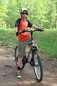 Teenager v lese na kole — Stock fotografie