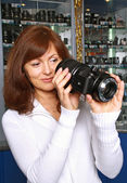 The girl-seller of phototechnics conside — Stock Photo