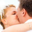 Bride kissing a groom with a smile — Stock Photo #1133505