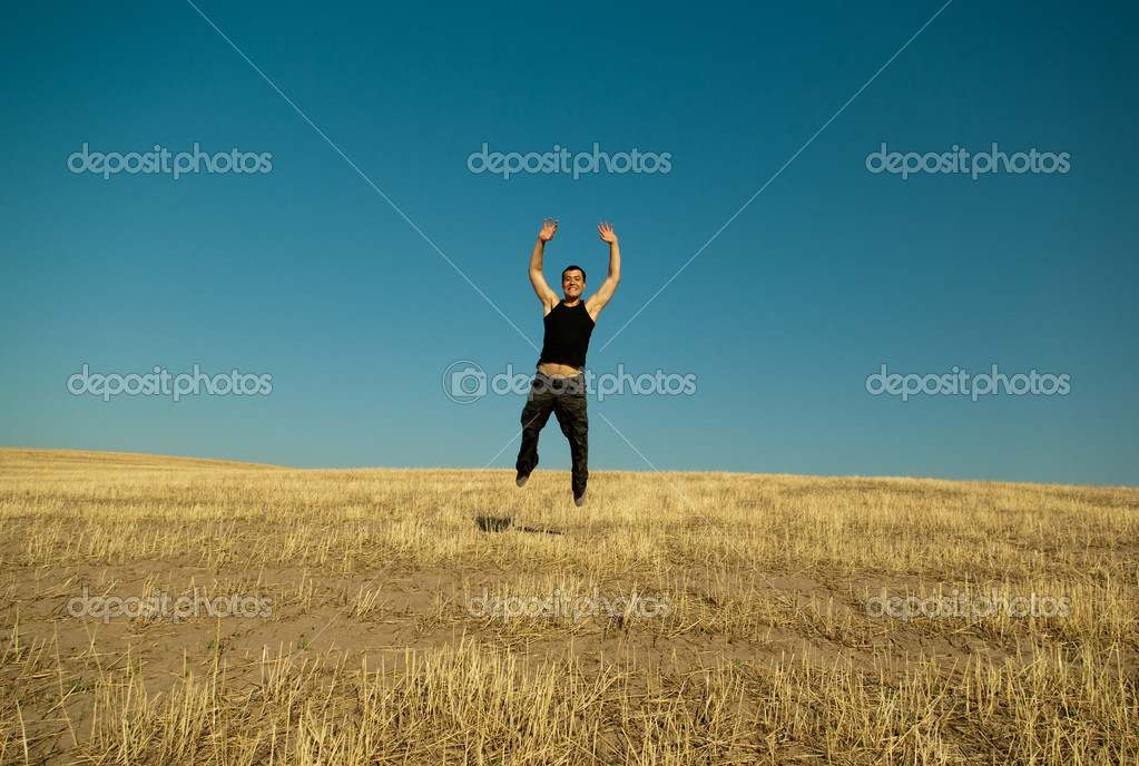 Young handsome asian man jumping joyfully in the barley meadows — Stock Photo #1134125
