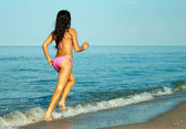 Running girl in bikini — Stockfoto
