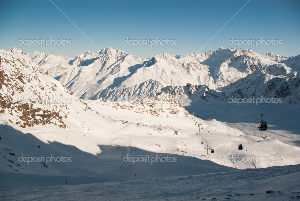 Beautiful rocky mountains in Alps covered with snow with skiing pistes and ski lifts — Stock Photo #1542572