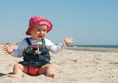 Cute little girl sitting in the sand — Stock Photo