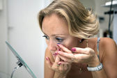 Woman inserting a contact lens — Stockfoto