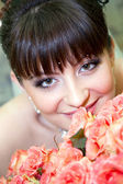 Beautiful bride with bouquet of roses — Stock Photo