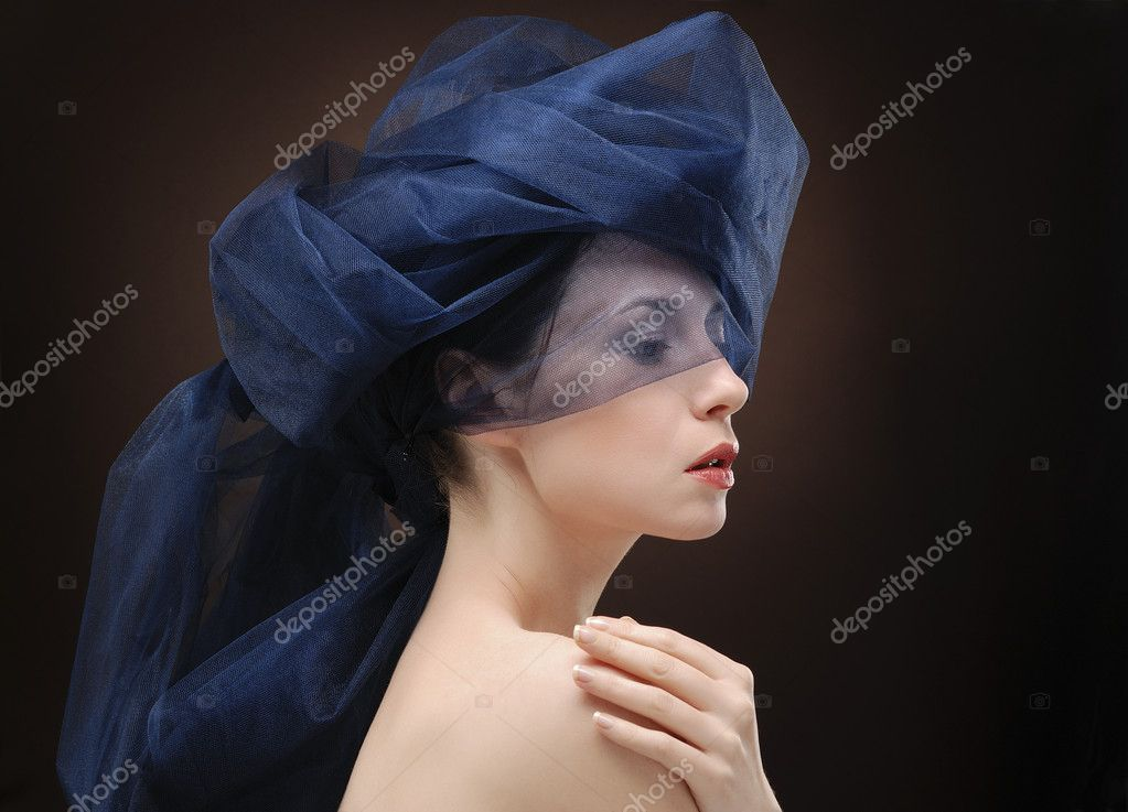 Portrait of young beautiful woman folding fabric round her head — Stock Photo #1267684
