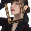 Woman looking through picture frame — Stockfoto