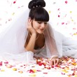 Beautiful bride and rose petals — Stock Photo