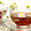 Stock Photo: Cups of tea and chamomile blossoms