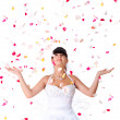 Cute bride throws rose petals — Stock Photo