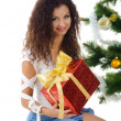 Cute young woman near christmas tree — Stok fotoğraf