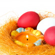 Eggs and candle in a small nest - Stock Photo
