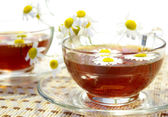 Cups of tea and chamomile blossoms — Stock Photo