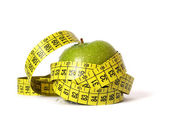Green apple and tape measure — Stock Photo